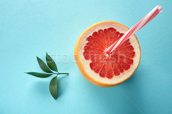 Half a grapefruit in the form of a glass with a drinking tube and a green leaf on a blue background Stock photo © artjazz