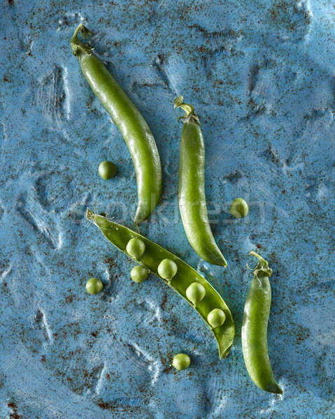 Fresh green peas with pods on a blue ceramic background. Close-up top view. Stock photo © artjazz
