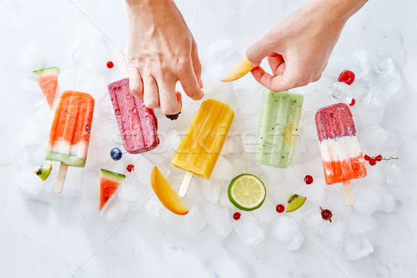 The woman's hands decorate the ice cream on a stick with bits of juicy fruit. Summer dessert. Flat l Stock photo © artjazz