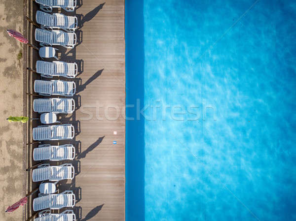 Beach chairs near swimming pool, top view Stock photo © artjazz