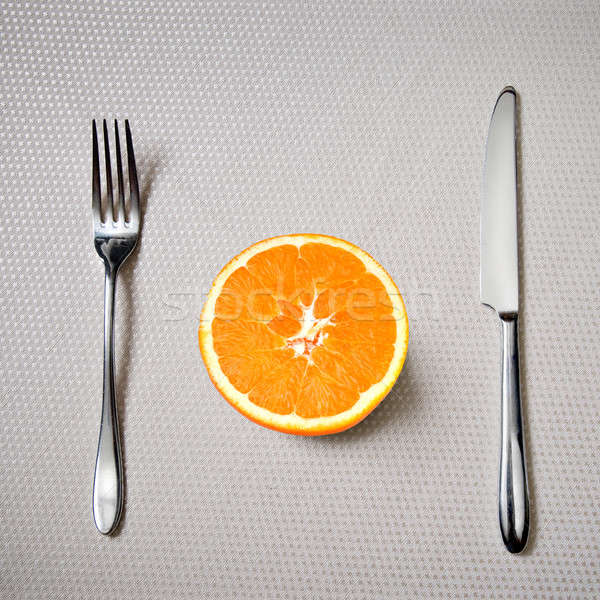 Healthy breakfast - fresh orange with knife and fork Stock photo © artjazz