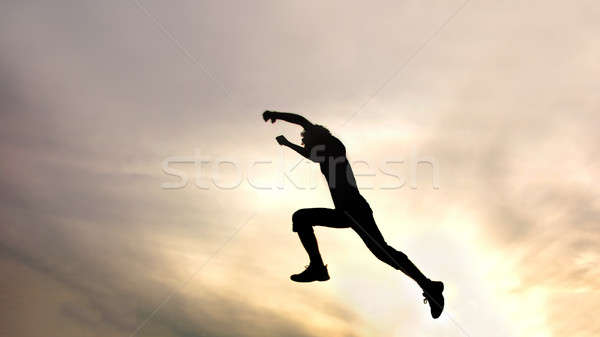 silhouette of jumping boy against sky Stock photo © artjazz