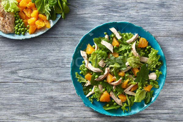 Natural fresh salad from lettuce, green peas, slices of orange and chicken on a blue ceramic plate o Stock photo © artjazz