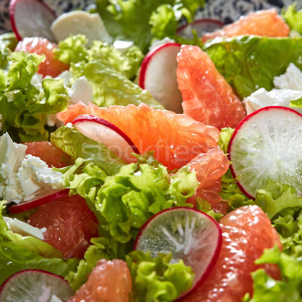 Natural fresh salad from lettuce, grapefruit, slices of radish and cheese. Close-up view from above. Stock photo © artjazz