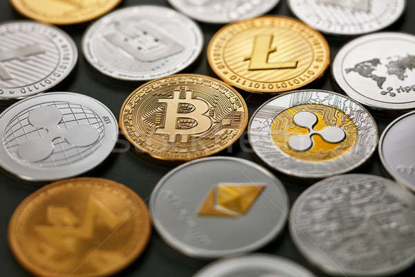 Set of different gold and silver coins of crypto-currencies on a dark background with bright light.  Stock photo © artjazz
