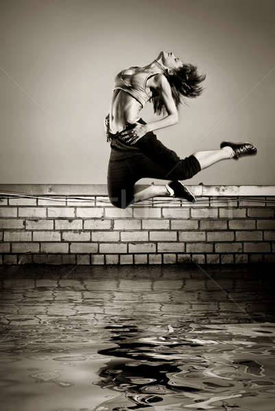 black and white photo of girl jumping on the roof in the water  Stock photo © artjazz