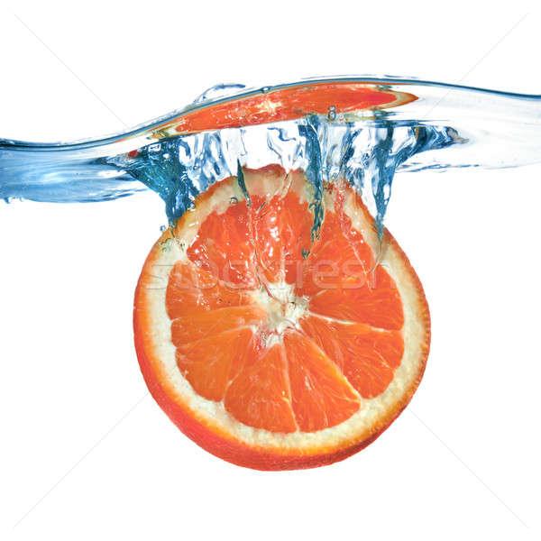 Fresh grapefruit dropped into water with splash isolated on white Stock photo © artjazz