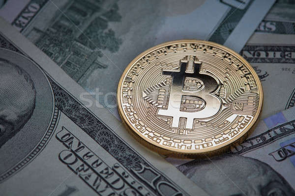 Dollar bills and gold coin bitcoin. Cryptocurrency business concept. Stock photo © artjazz