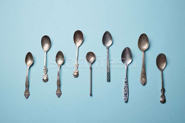 Stainless steel small kitchen dessert spoon isolated on blue Stock photo © artjazz