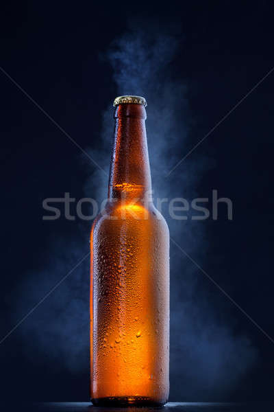 Cold beer bottle with drops, frost and vapour on black Stock photo © artjazz