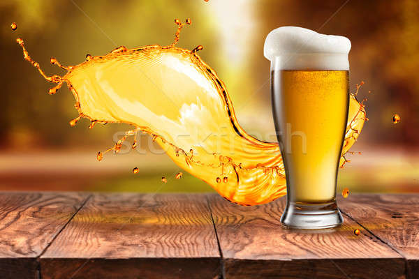 Beer in glass with splash on wooden table against autumn leaves Stock photo © artjazz