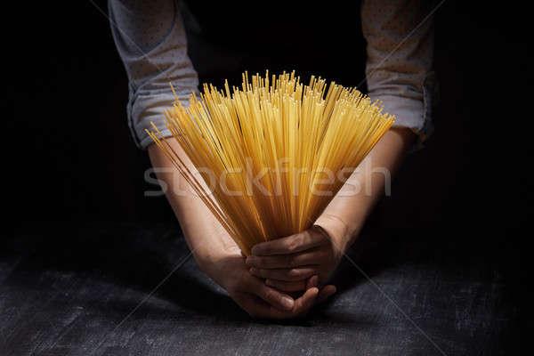 Női kezek tart spagetti tészta fa asztal Stock fotó © artjazz