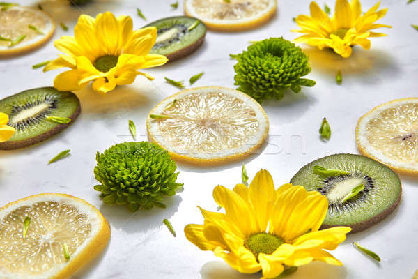 Natural organic diagonally floral patter from spring flowers, kiwi and lemon slices. Summer flowers  Stock photo © artjazz