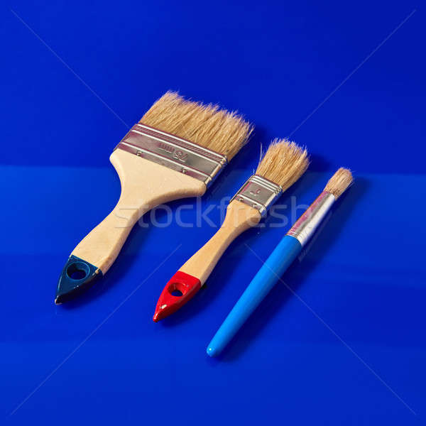 The set of brushes for painting the surface and apartment repair on a blue background. Stock photo © artjazz