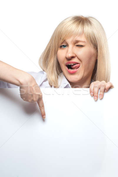 Stock photo: Attractive funny woman holding white empty paper and pointing on it isolated on white