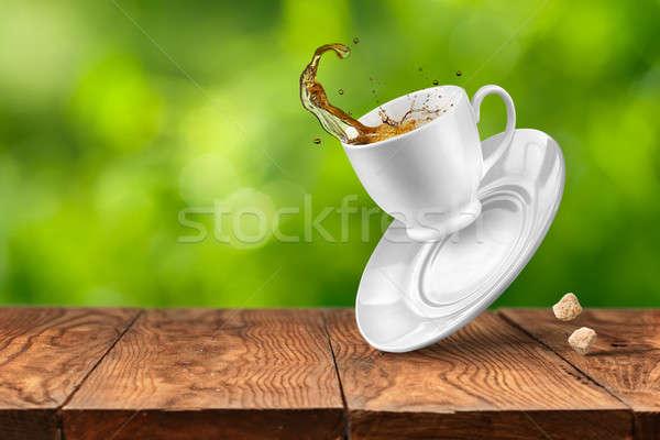 Splash of tea on wooden table against green background Stock photo © artjazz