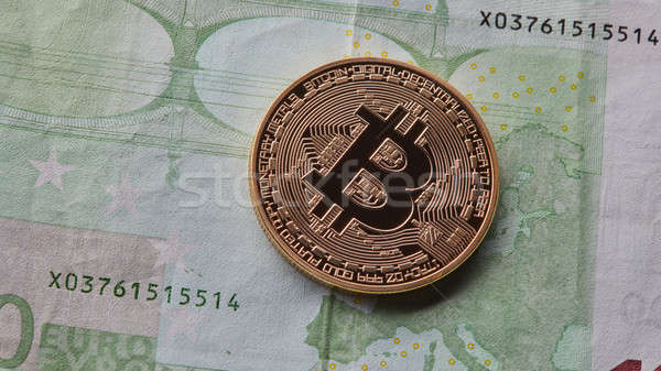 One gold coin of bitcoin on the background of euro. Stock photo © artjazz