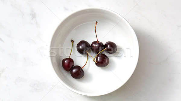 Tasty summer natural fresh fruits cherries on a white plate on concrete table. Stock photo © artjazz