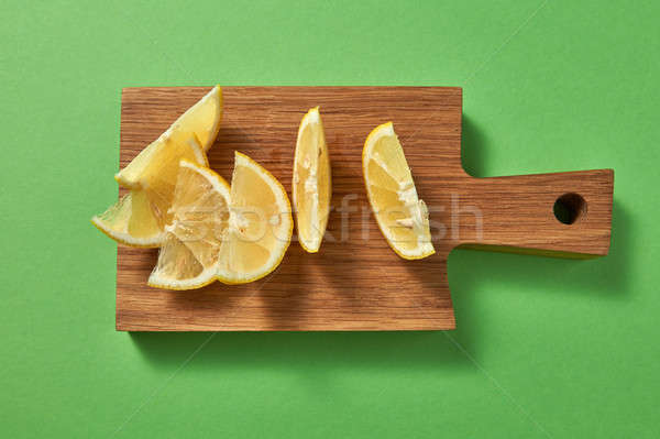 Slices of juicy ripe natural yellow lemon on a wooden board on a green background. Top view. Stock photo © artjazz