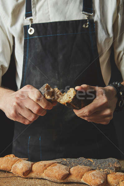 halves of baguette in the hands of a baker Stock photo © artjazz