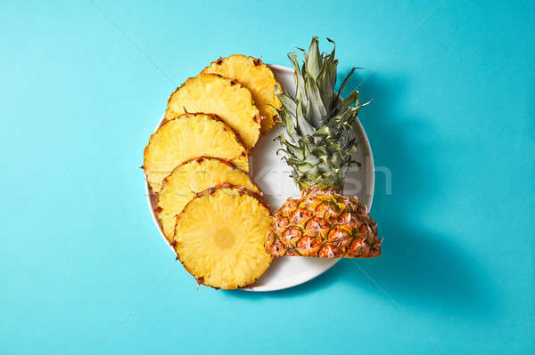 Stock photo: round pieces of pineapple on a white plate on a blue background