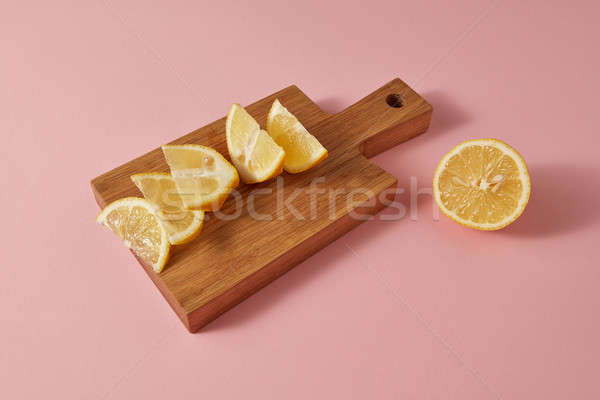 Juicy slices and half of natural yellow lemon on a wooden board on a pink background. Copy space. Stock photo © artjazz