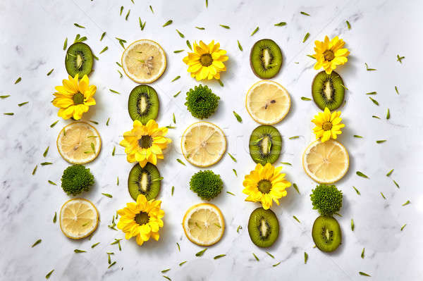Floral background. Flowers pattern from yellow, green flowers, slices of kiwi and lemon. Flat lay. Stock photo © artjazz