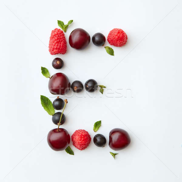 Fresh fruits pattern of letter E english alphabet from natural ripe berries - black currant, cherrie Stock photo © artjazz