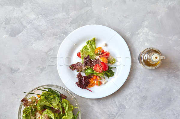 Two plates with fresh salad on a gray background Stock photo © artjazz