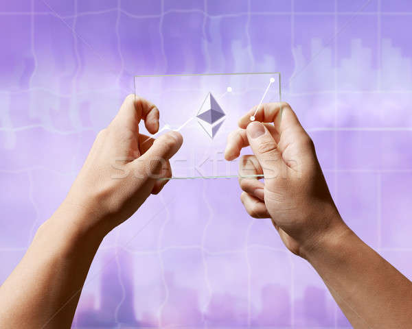A man holds a glass screen with Icons of ethereum and a crypto currency graph Stock photo © artjazz