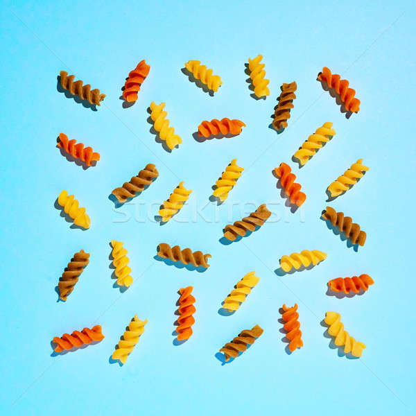 Pattern of multi-colored pasta on a blue background. Flat lay. Stock photo © artjazz