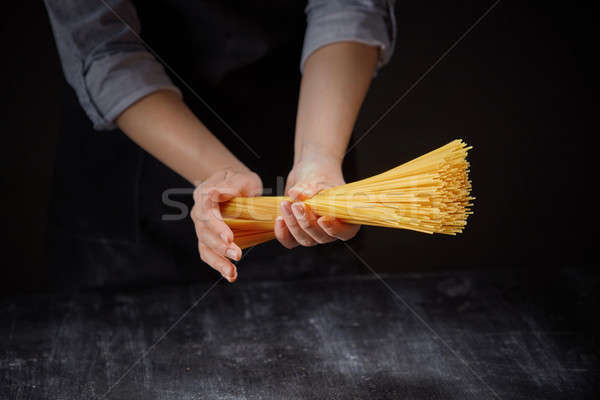 Raw italian pasta in female hands on dark background Stock photo © artjazz