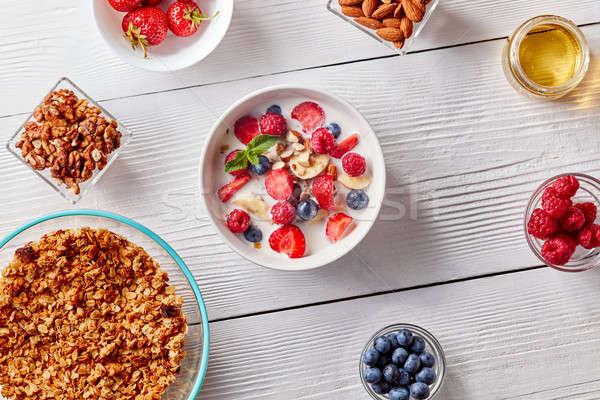 Homemade granola in a plate, sliced banana, berries, almonds, walnuts and white bowl with natural or Stock photo © artjazz