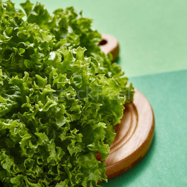 Organic natural green lettuce salad on a wooden board on a green background. Stock photo © artjazz