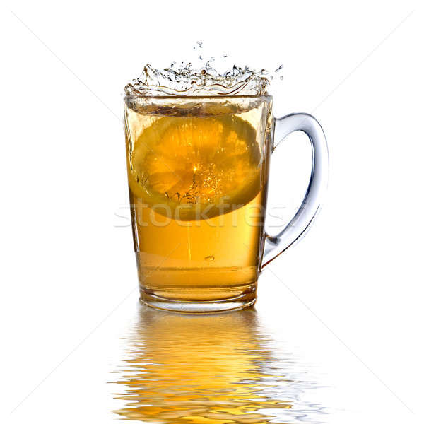 lemon dropped into tea cup with splash and reflection isolated on white Stock photo © artjazz
