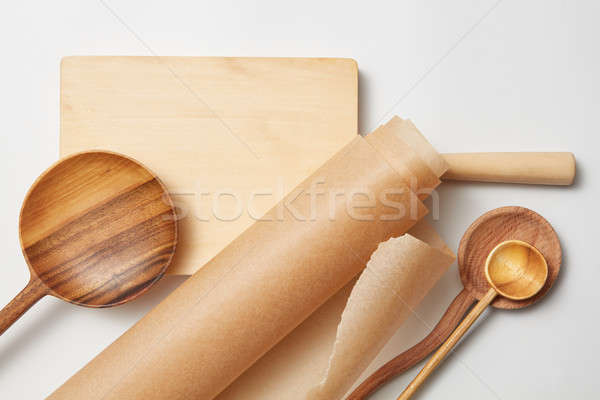 roll baking paper and various wooden spoons Stock photo © artjazz