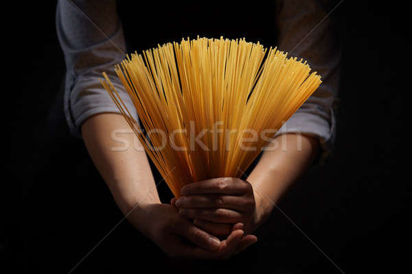 Woman's hands with gluten free spaghetti made from rice and maize on dark background Stock photo © artjazz