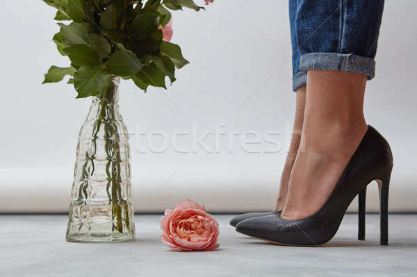 On the floor is one pink rose, a glass vase with green branches near the legs of a girl shod with bl Stock photo © artjazz
