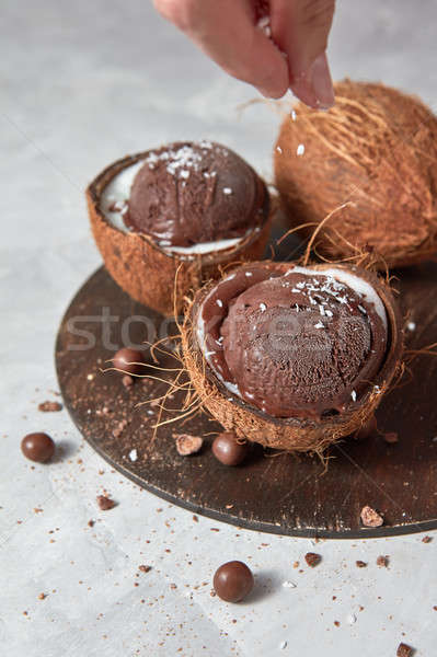 Female hand coconut sprinkles on chocolate ice cream in coconut  Stock photo © artjazz