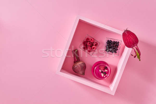 Glass with beetroot berry smoothies on a pink background with a wooden frame with copy space. Top vi Stock photo © artjazz