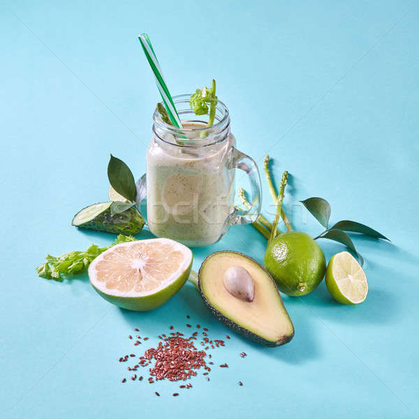 Homemade green smoothies with slices lemon, lime, avocado, selery, cucumber with flax seeds on a blu Stock photo © artjazz