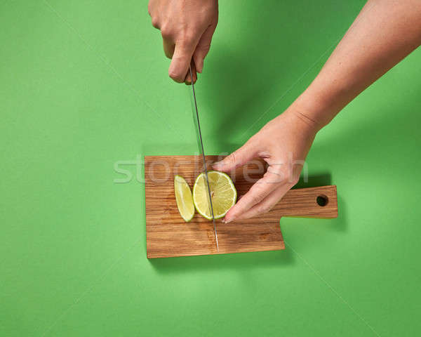 Wooman hands cut a juicy green ripe lime to slices with knife on a wooden cutting board on a green.  Stock photo © artjazz