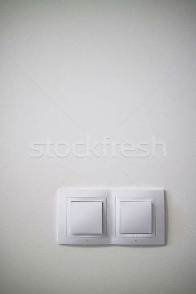 Electric two white lighting switchs on concrete wall Stock photo © artjazz