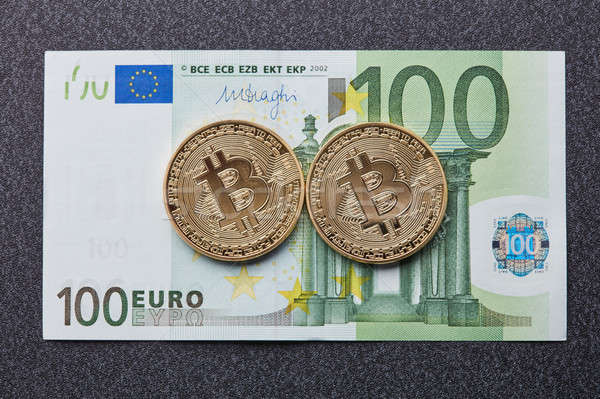 Two gold coins bitcoin on a hundred euro banknote on a dark background Stock photo © artjazz