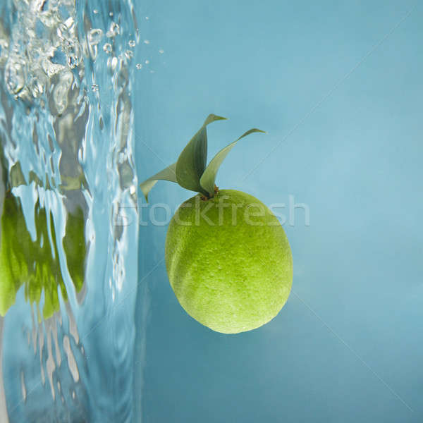 Stock photo: Round green lime with leaves in water on a blue background