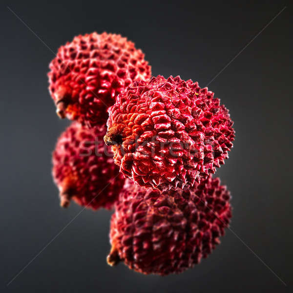 Tropical ripe litchi fruit isolated on a black glossy background Stock photo © artjazz