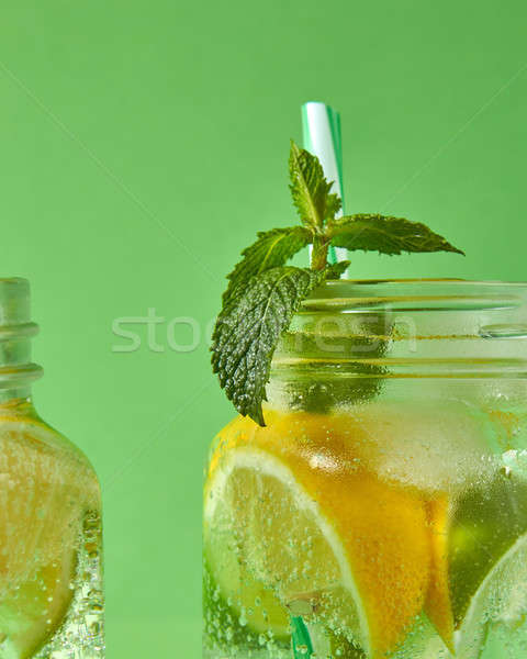 A sprig of green mint in focus in a glass jar with a refreshing natural handmade cocktail. Citrus fr Stock photo © artjazz