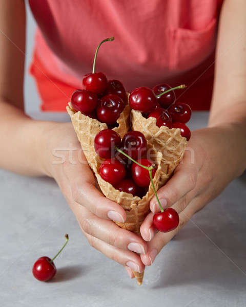 A woman holds a wafer cones with juicy red cherry fruits above a Stock photo © artjazz
