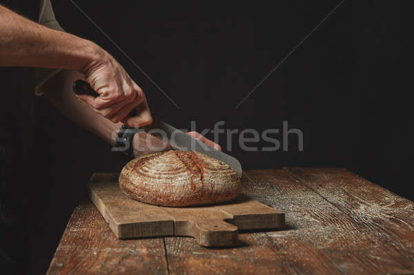 Man slicing tasty fresh bread. Stock photo © artjazz