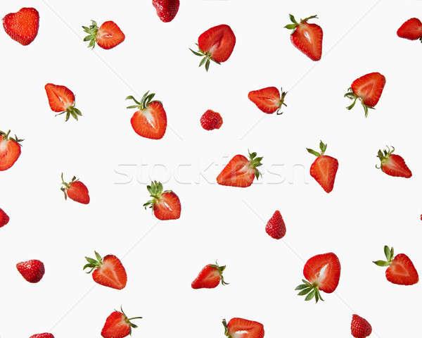 Pattern of fresh halves of ripe strawberries on a gray background Stock photo © artjazz